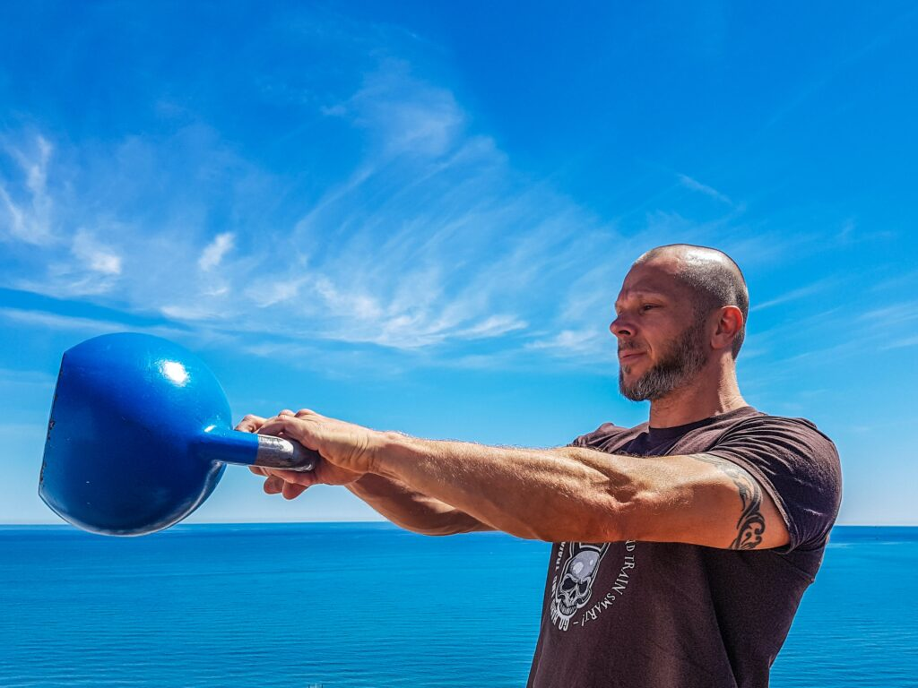 man using kettlebell in a cardio workout